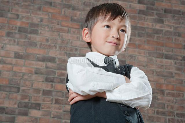腕を組み考える子供 サラリーマンイメージの写真素材 [FYI01433233]