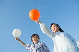 風船を持ち笑顔の男の子と女の子の写真素材 [FYI01433292]