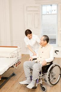 車椅子のシニア男性をフォローする女性介護士の写真素材 [FYI01433478]