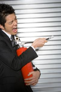 消火器を持ったビジネスマンの写真素材 [FYI01433579]