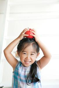リンゴを持つ笑顔の幼稚園児の写真素材 [FYI01433687]