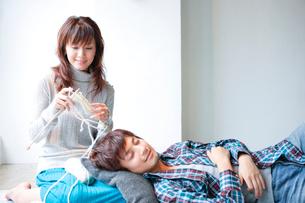 編物をする女性と寝転ぶ男性の写真素材 [FYI01433769]