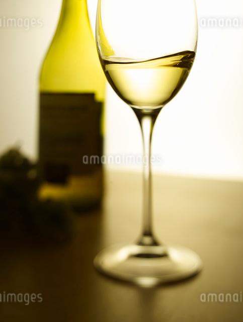グラスに入った白ワインとワインのボトルの写真素材 [FYI01433783]