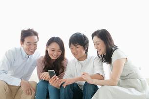 ソファーでスマートフォンを楽しむ家族の写真素材 [FYI01433834]
