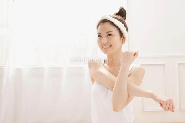 ルームウェア姿でストレッチをする女性の写真素材 [FYI01433951]