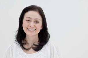 白バックで微笑み見つめるシニア女性の写真素材 [FYI01433986]