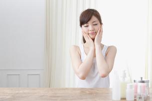 手で両頬を抑える女性の写真素材 [FYI01434095]