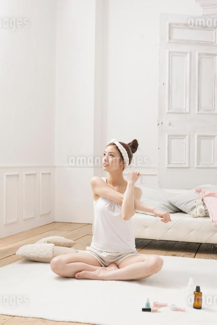 ルームウェア姿でストレッチをする女性の写真素材 [FYI01434127]