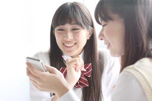 携帯電話を一緒に見る高校生2人の写真素材 [FYI01434138]