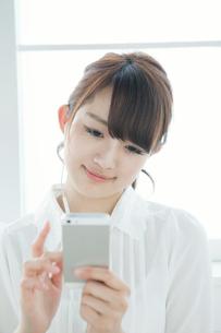 携帯で音楽を聴く女子大生の写真素材 [FYI01434188]
