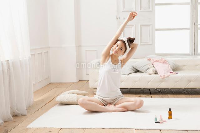 ルームウェア姿でストレッチをする女性の写真素材 [FYI01434211]