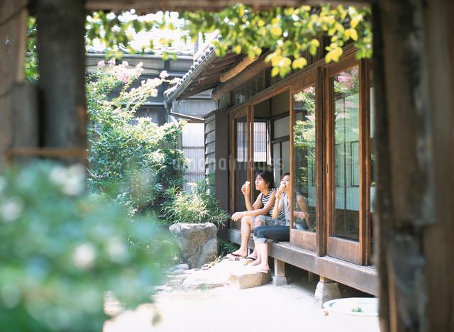 縁側に座りソフトクリームを食べる日本人カップルの写真素材 [FYI01434225]