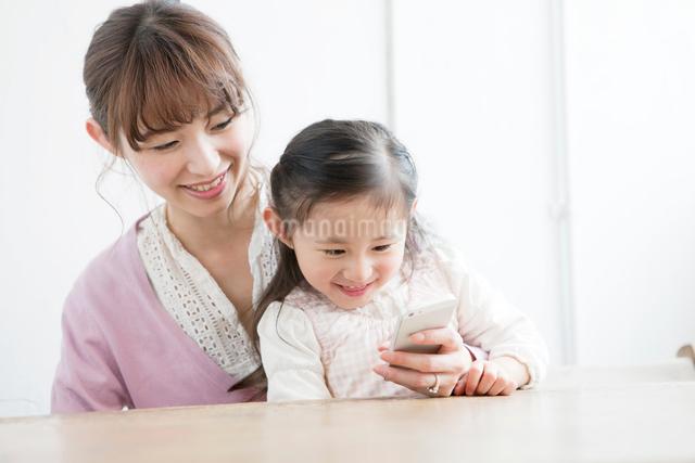 一緒に携帯電話を見る母親と娘の写真素材 [FYI01434368]