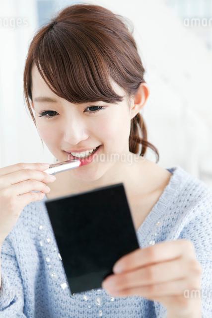 口紅を塗る女子大生の写真素材 [FYI01434402]