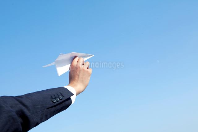 紙飛行機を持つ20代ビジネスマンの手の写真素材 [FYI01434485]