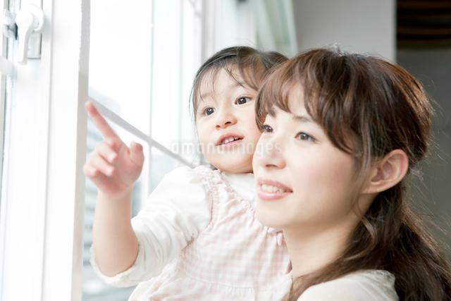 窓から外を眺める母親と娘の写真素材 [FYI01434811]