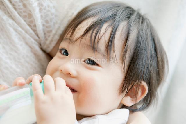 ミルクを飲み微笑む赤ちゃんの写真素材 [FYI01434824]