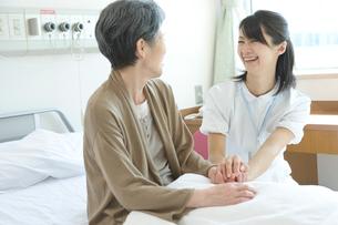 年配患者と話す笑顔の看護師の写真素材 [FYI01434856]