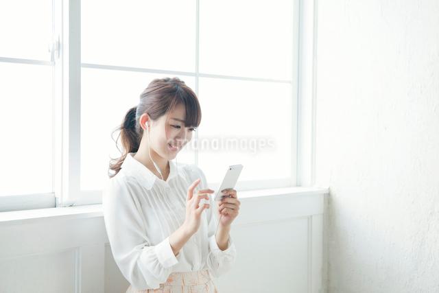 携帯で音楽を聴く女子大生の写真素材 [FYI01434925]