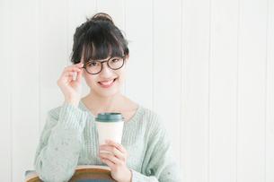 眼鏡のフレームを持つ20代女性ポートレートの写真素材 [FYI01434941]