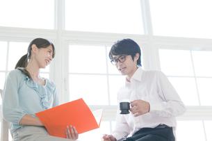 座りながら話すビジネスマンとビジネスウーマンの写真素材 [FYI01434975]