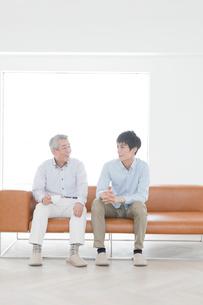 ソファに座って話す笑顔の父親と息子の写真素材 [FYI01435005]