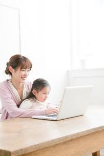 一緒にパソコンを見る母親と娘の写真素材 [FYI01435092]