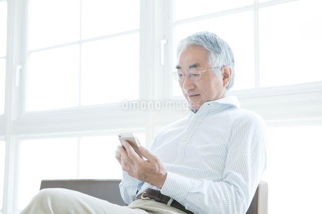 携帯電話を見る中年男性の写真素材 [FYI01435139]