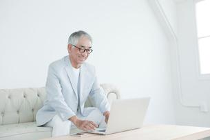 ソファに座りノートパソコンを使う中高年男性の写真素材 [FYI01435147]