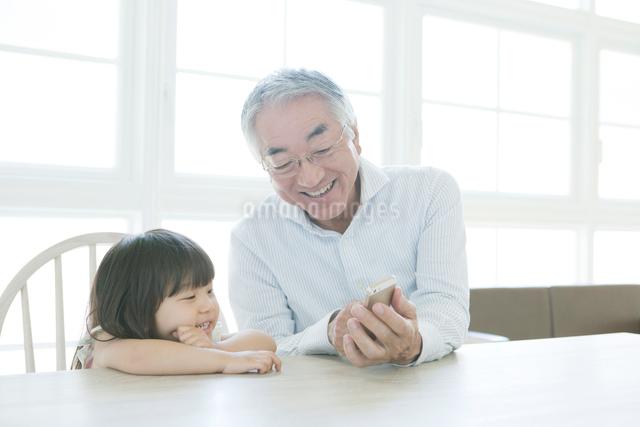 孫娘と携帯電話を見るシニア男性の写真素材 [FYI01435212]