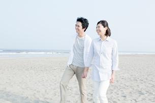 海辺を散歩するカップルの写真素材 [FYI01435237]