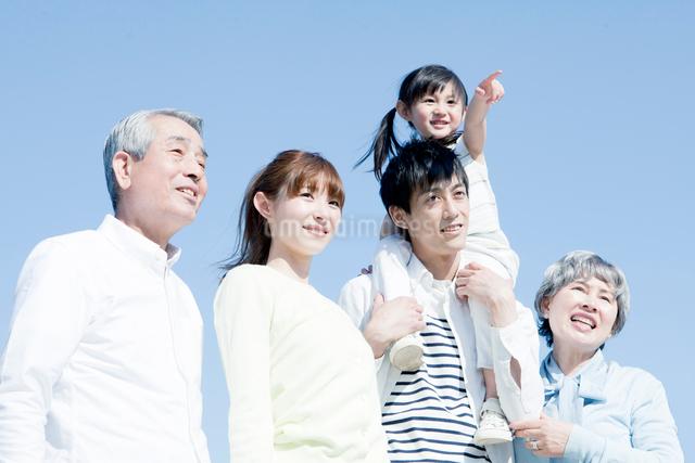 青空の下に立つ三世代家族の写真素材 [FYI01435266]