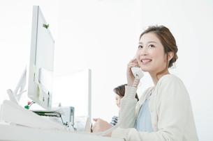 オフィスで電話を使うヤングビジネスウーマンの写真素材 [FYI01435343]