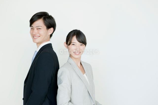 背中合わせのヤングビジネスマンとウーマンの写真素材 [FYI01435388]