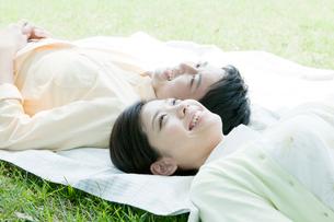 レジャーシートに寝転ぶカップルの写真素材 [FYI01435399]