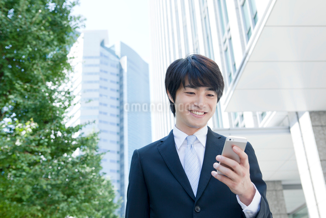 携帯電話を見る笑顔のヤングビジネスマンの写真素材 [FYI01435444]