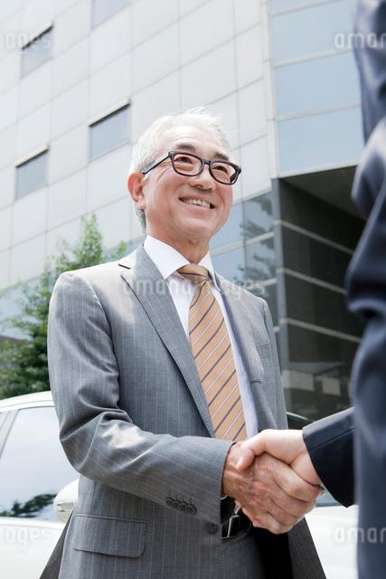 車の前で握手をする中高年ビジネスマンの写真素材 [FYI01435445]