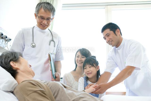 患者を見守る家族と医師の写真素材 [FYI01435465]