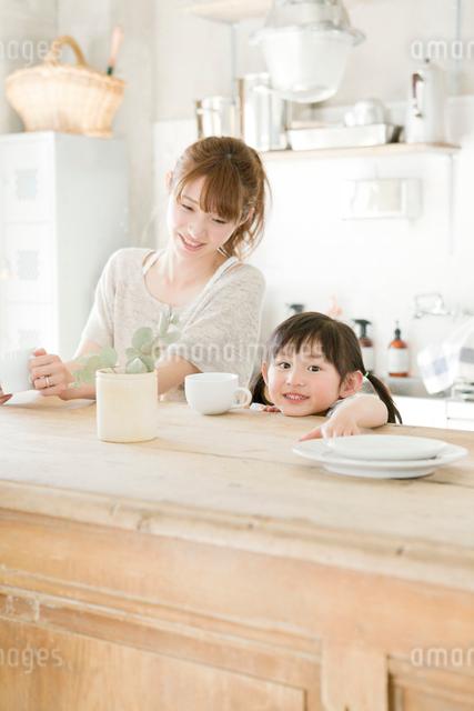 キッチンでくつろぐ母親と娘の写真素材 [FYI01435519]