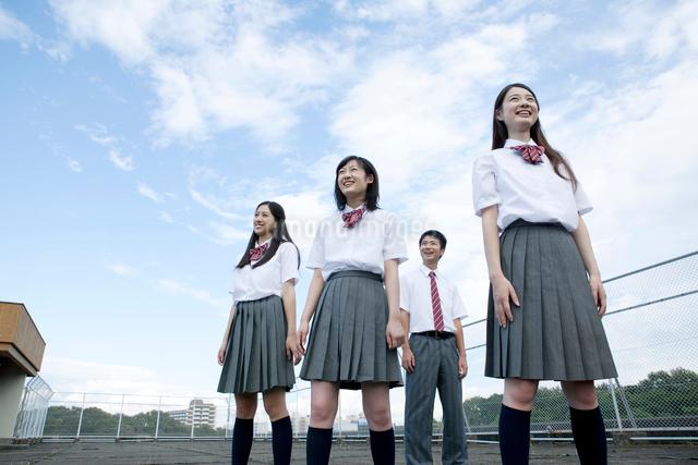 空と雲を背景に立つ高校生の写真素材 [FYI01435550]
