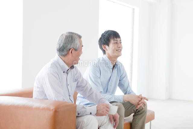 ソファに座って話す笑顔の父親と息子の写真素材 [FYI01435555]