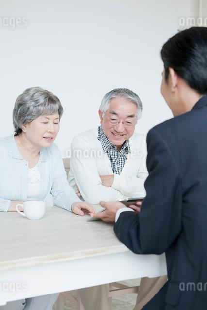 アドバイスを受けるシニア夫婦の写真素材 [FYI01435612]