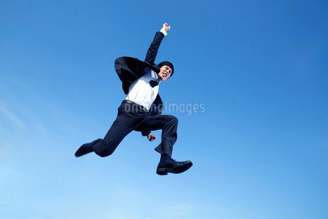 ジャンプする20代ビジネスマンの写真素材 [FYI01435655]