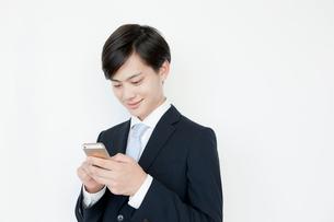 携帯電話を使うヤングビジネスマンの写真素材 [FYI01435660]