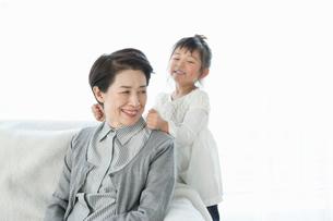 肩をたたく孫と笑顔の祖母の写真素材 [FYI01435700]