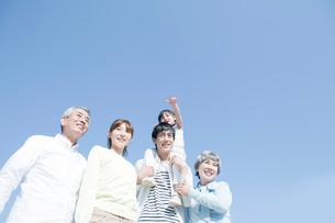 青空の下に立つ三世代家族の写真素材 [FYI01435884]
