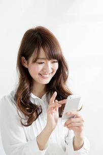 携帯電話を操作する女子大生の写真素材 [FYI01435895]