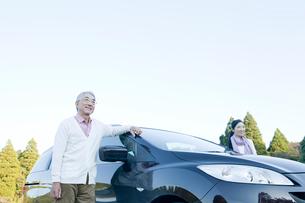 車の横で景色を見るシニアカップルの写真素材 [FYI01435942]