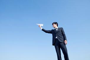 紙飛行機を持つ20代ビジネスマンの写真素材 [FYI01435946]