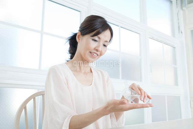 化粧水を手にとる中年女性の写真素材 [FYI01436126]